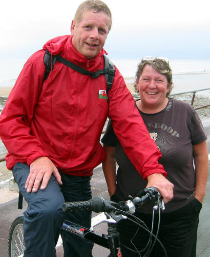 Photo of Paul Edwards on his bike with his wife standing alongside