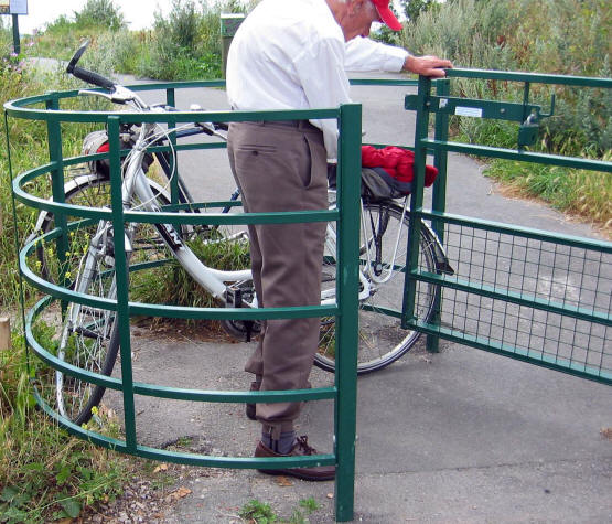 Photo of cyclist struggling to get his bike through a very tight kissing gate