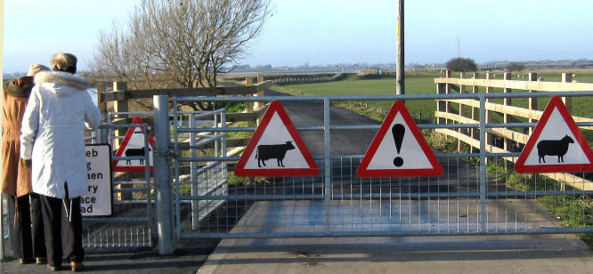 Photo of two pedestrians going through a gate that has 4 animal warning signs