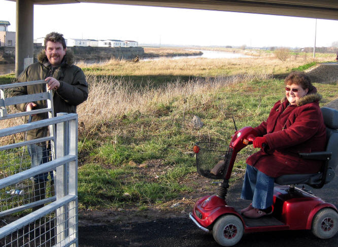 Photo of a lady in an electric buggy about to pass through a gate with the assistance of a companion