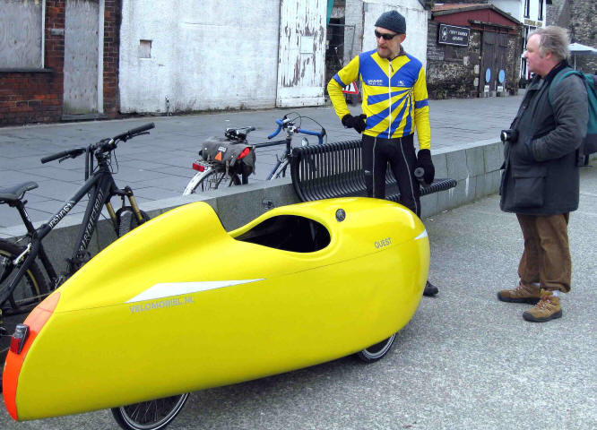 photo of Jeremy Taylor standing beside his recumbent tricycle on Conwy quay