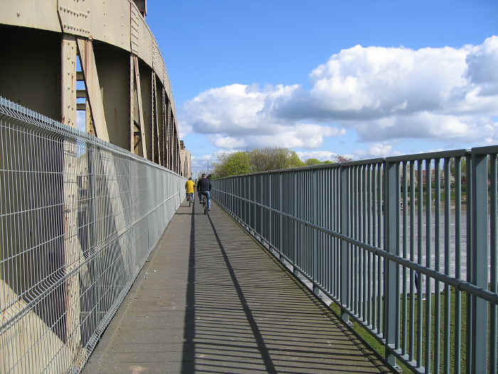 Cyclists crossing river Dee by the cyclepath that has been added on to the side of the Hawarden bridge