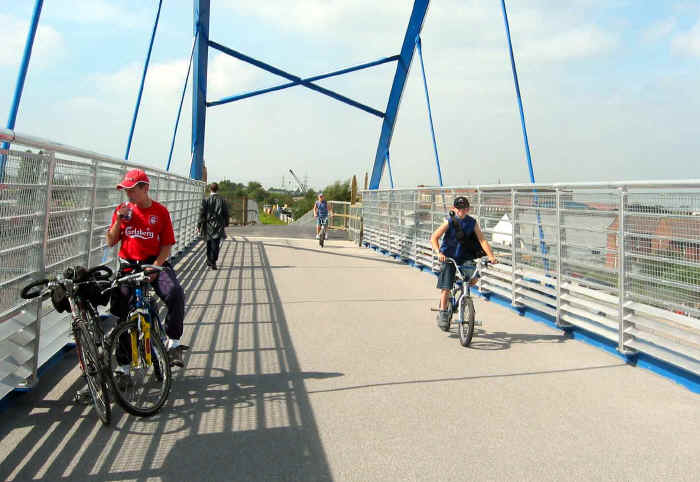 Several cyclists and a pedestrian on the bridge at Drome Corner