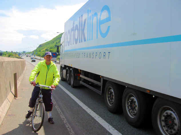 Cyclist on narrow path alongside A55 expressway close to a large passing vehicle