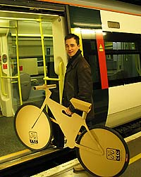 Young man boarding a train with a cardboard cut-out of a cycle