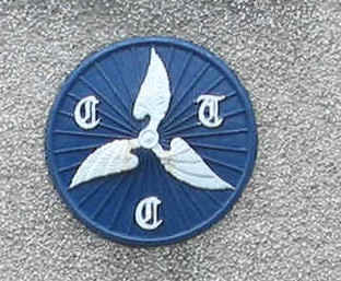 Close-up of a blue painted CTC winged wheel sign on a wall