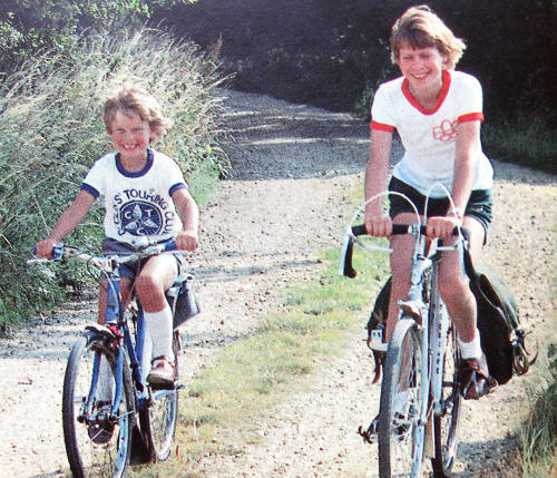 Photo of two children cycling bareheaded