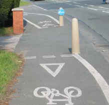 A cycle path at Dyserth has give-way lines across it where it crosses a drive together with posts on both sides
