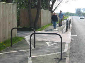 A cycle path at Rhyl with steel barriers to force cyclists to dismount where the path crosses the entrance to a drive