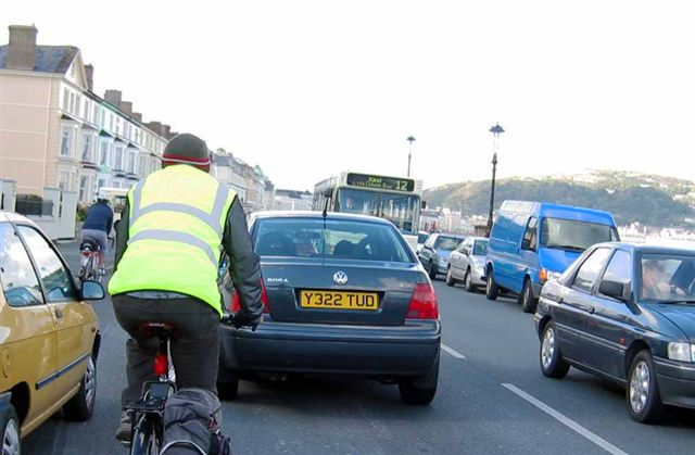 Cyclist being closely overtaken by heavy traffic on Llandudno's coast road