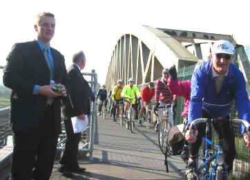 Cyclists cross by new bridge path at its official opening
