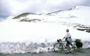 Pat stands with the tandem before a large snow field on the Col d'Allos in the Alps