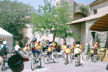 Large group of child cyclists in a provencal village square