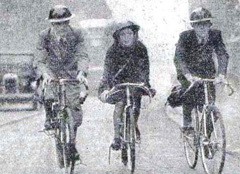 Photo of 3 cyclists riding their bikes and wearing tin hats during World War 2