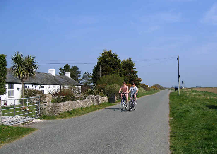 Cyclists on the road between Malltraeth and Pont Marquis