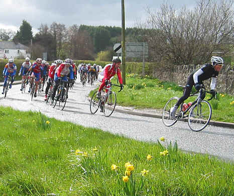 Racing cyclists round a bend at Bodfari