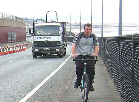 Photo of Colin Howard cycling on pavement