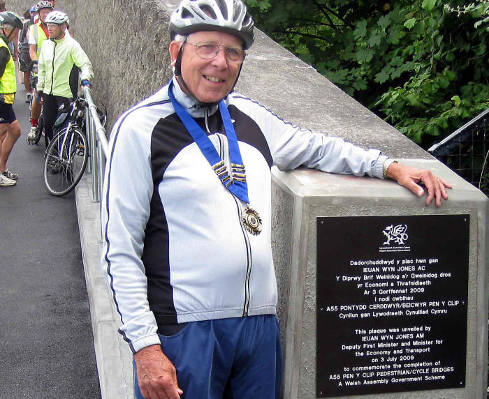 Photo of Mike Cross standing by the official plaque