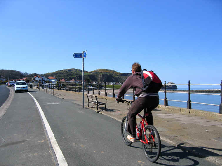 Cyclist on the cycle path alongside the road at Penrhyn Bay