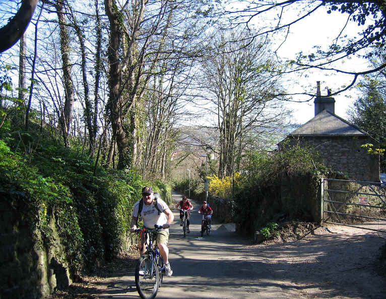 Cyclists struggling up steep hill at Penrhyn Bay