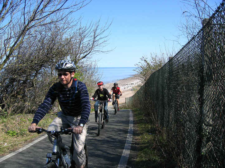 Cyclists ascending the steep hill on cycleway at Llanddulas
