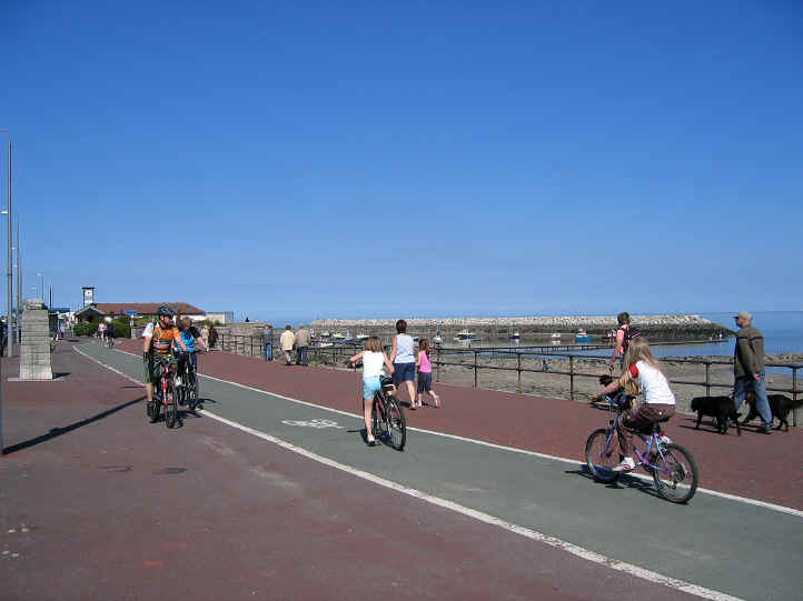 Child cyclists Approaching the breakwater and little harbour at Rhos on Sea