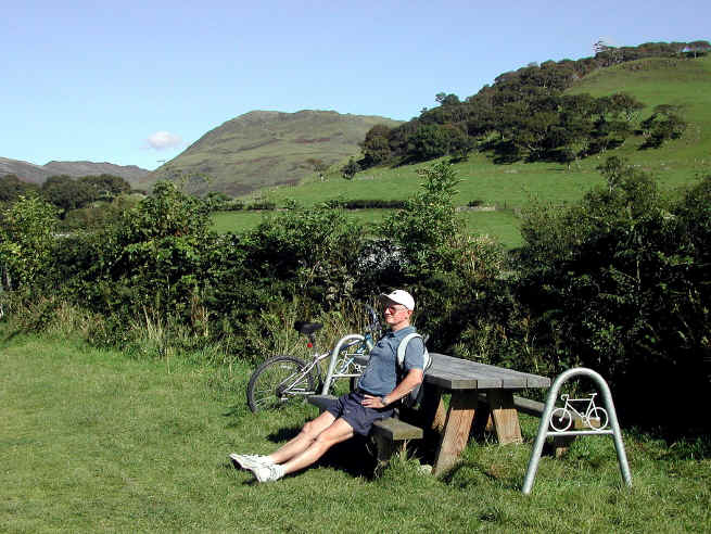 A cyclist rests at a picnic bench in the Dysynni valley near Tywyn where there are artistic cycle stands and benches