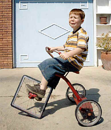 Small boy, crying, sitting on a tricycle the front wheel of which is square