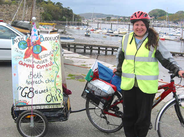 Environmental campaigner, Lydia Bulmer, pauses with her bicycle and trailer with poster at Conwy