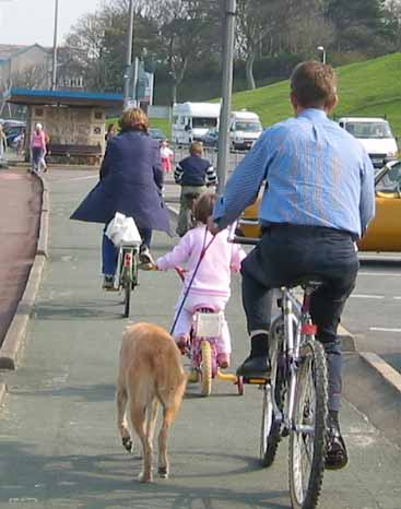 Parents and young child cycle on Colwyn prom cycleway - the father has the family dog on a lead