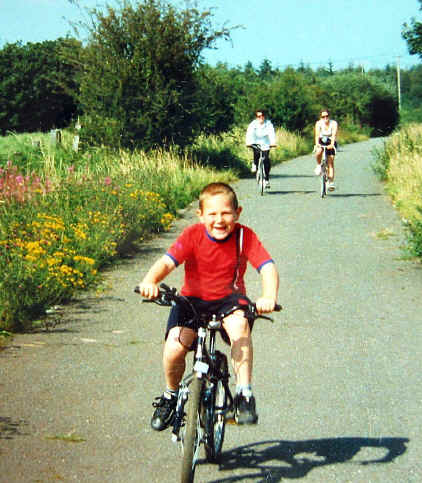 Small boy on a cycle enjoying a ride on Lon Eifion with his parents some way behind
