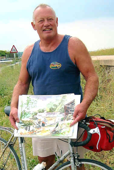 Artist Barry Drew poses with one of his painting across his cycle crossbar