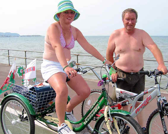 David Hayes with a bike and his wife, Jill, on a tricycle with rear container on Colwyn prom