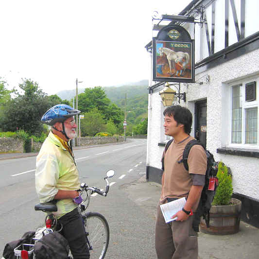 Cyclist pauses to chat with an Asian visitor outside the Y Bedol inn in the Conwy valley