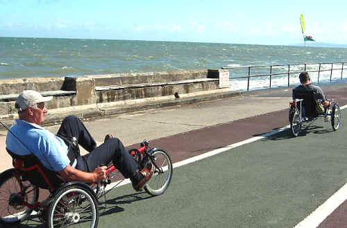 Severely disabled Paul Trigg with a foot propelled recumbent trike on Colwyn prom accompanied by his father also on a recumbent trike