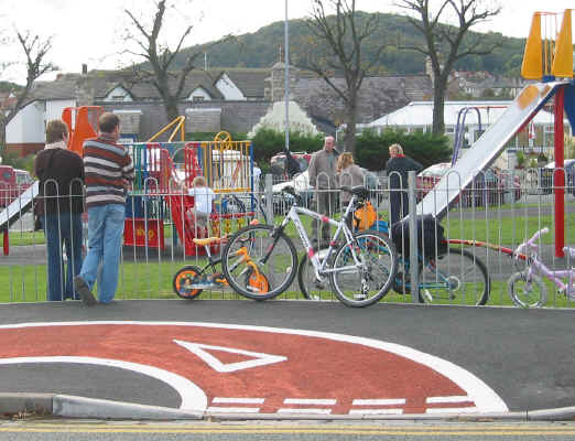 Cyclepath passing by the railings of a children's play area with some children's bikes fastened to the railings