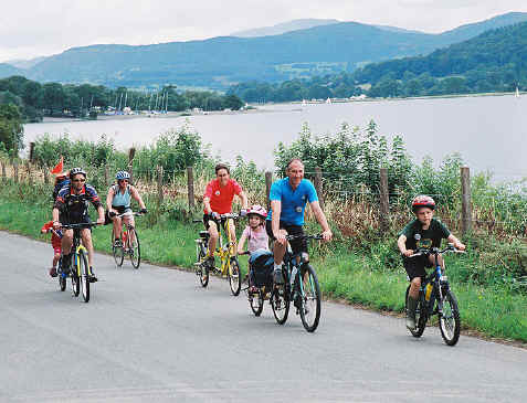 Group of cyclists, including small children, cycling alongside Lake Bala (Llyn Tegid)