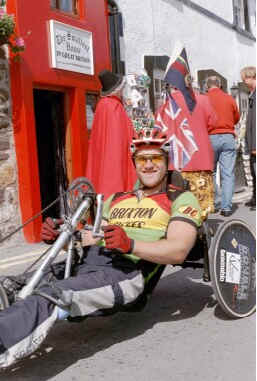 Dr David Abrutat on his recumbent cycle before the smallest house on Conwy quay