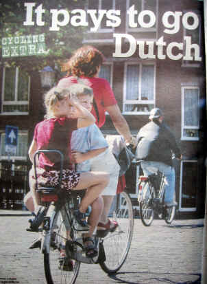 Lady cyclist in Groningen with two young children sitting face to face at the rear of her bike