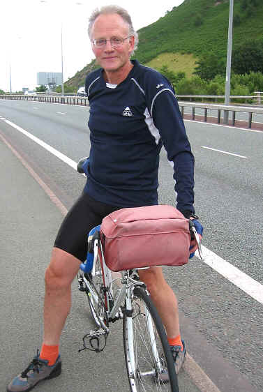 College lecturer commuting part way by bike on cycle path by side of A55 expressway