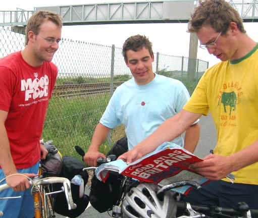 Three touring cyclists using a large road atlas