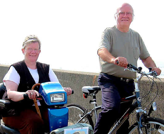 Husband and wife on cycleway with wife on a motorised buggy