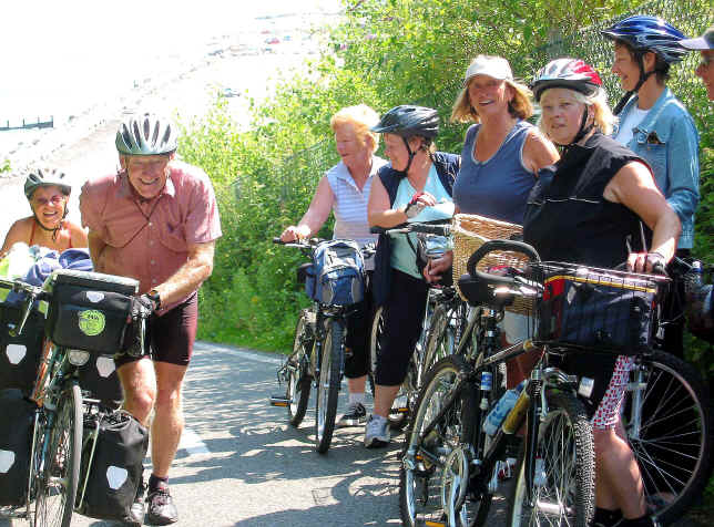Touring couple push their bikes up the steep hill on the cycleway near Llanddulas past a large group of lady cyclists