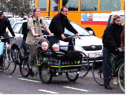City cyclists in Holland including a mother on a trke with young twins in a large front buggy