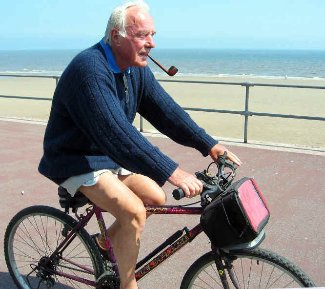 Cyclist with smoking pipe but without trousers or helmet riding along Colwyn prom