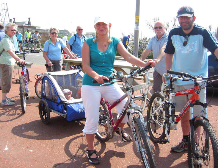 Photo of husband and wife with cycles. The wife is towing a buggy with a small, happy looking baby