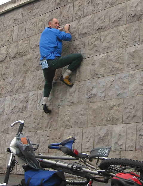 Photo of Bob Dickson climbing Colwyn Bay promenade wall with his bike at the bottom