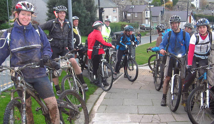 Photo of large group of muddy cyclists pausing at Conwy