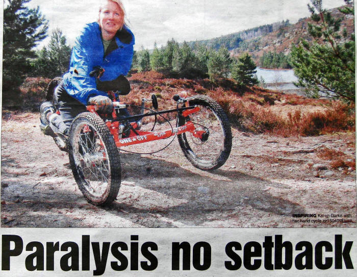Photo of Karen Darke riding a specially adapted tricycle propelled by using one hand only
