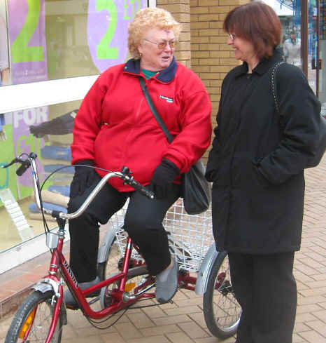 Mary, who has severe arthritis, on her adult tricycle meets a friend in Rhyl High Street